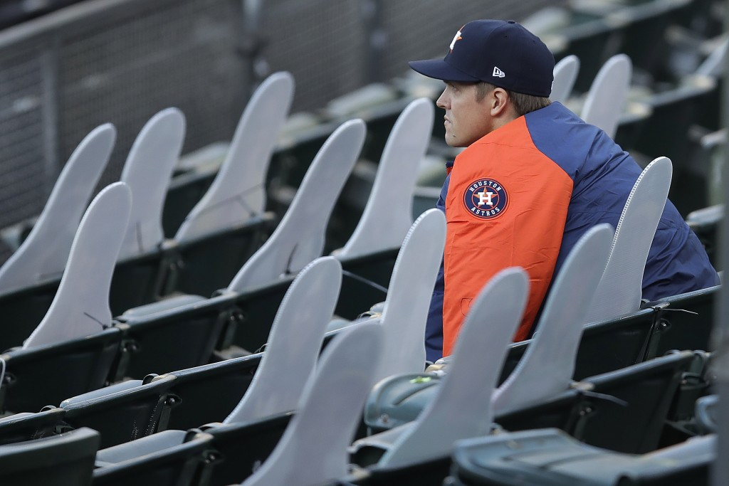 Houston Astros pitcher Zack Greinke socially distances himself beside cardboard cutout fans in the stands of the Oakland Coliseum in the fourth inning...