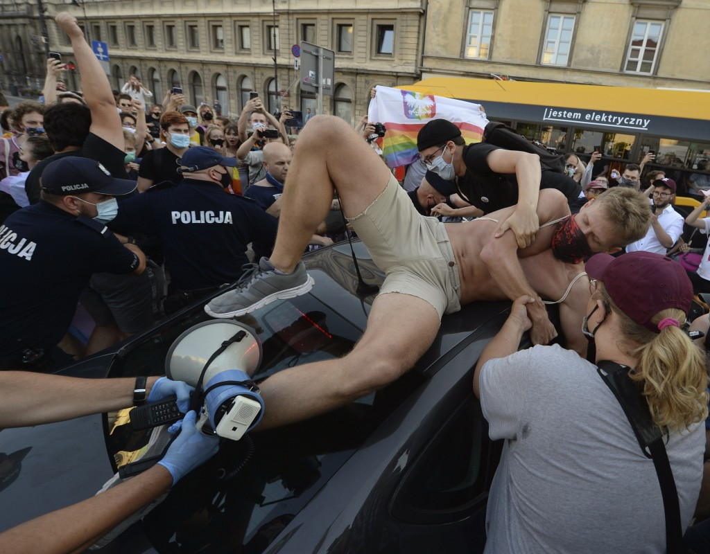 An activist climbs onto a police car to protest the detention of an LGBT activist in Warsaw, Poland, Friday, Aug. 7, 2020. The incident comes amid ris...