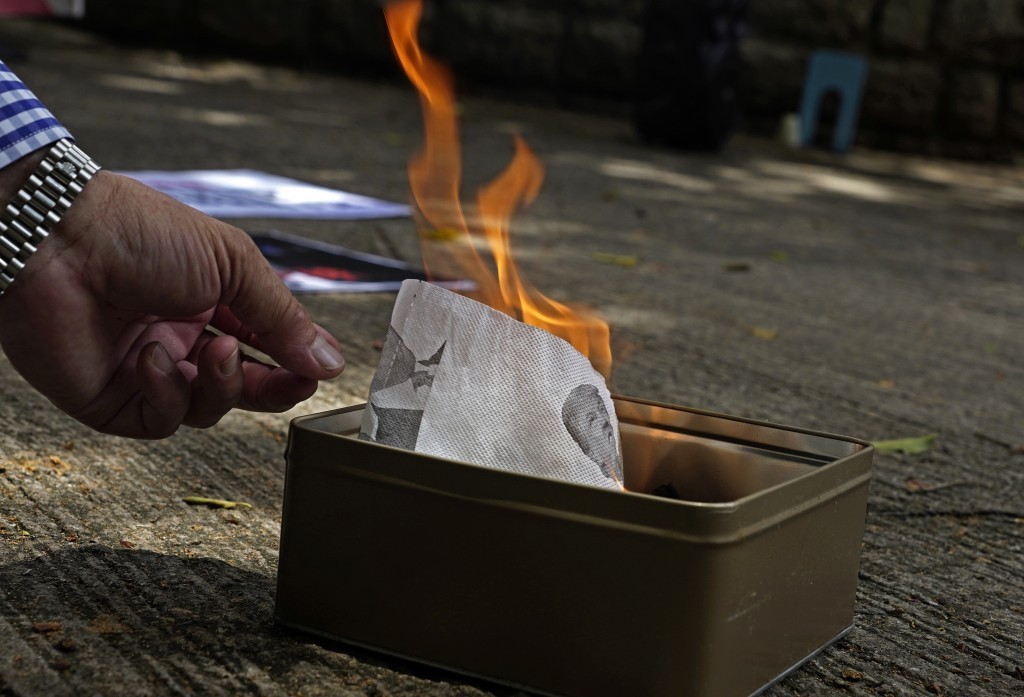 A pro-China supporter burns a picture of U.S. President Donald Trump during a protest against the U.S. sanctions outside the U.S. Consulate in Hong Ko...