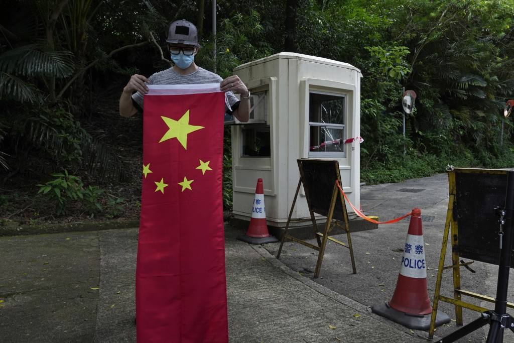 A pro-China supporter folds a Chinese national flag after a protest against the U.S. sanctions outside the U.S. Consulate in Hong Kong Saturday, Aug. ...