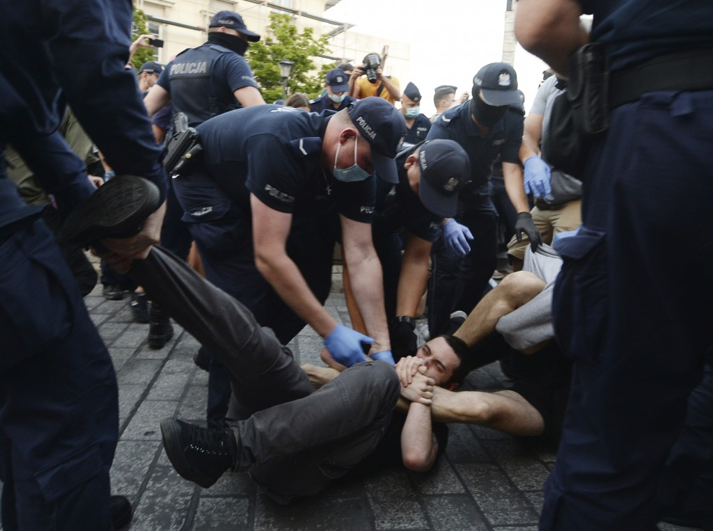 Police scuffle with pro-LGBT protesters angry at the arrest of an LGBT activist in Warsaw, Poland on Friday, Aug. 7, 2020. The incident comes amid ris...