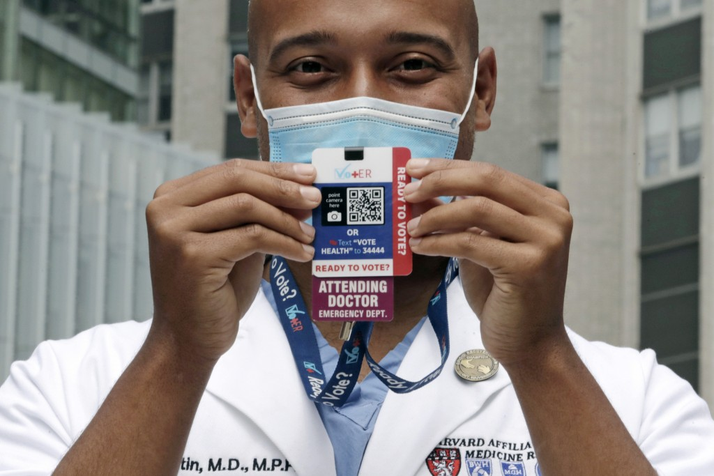 Alister Martin, an emergency room doctor at Massachusetts General Hospital, holds up a voter information card he wears on his ID lanyard, which gives ...