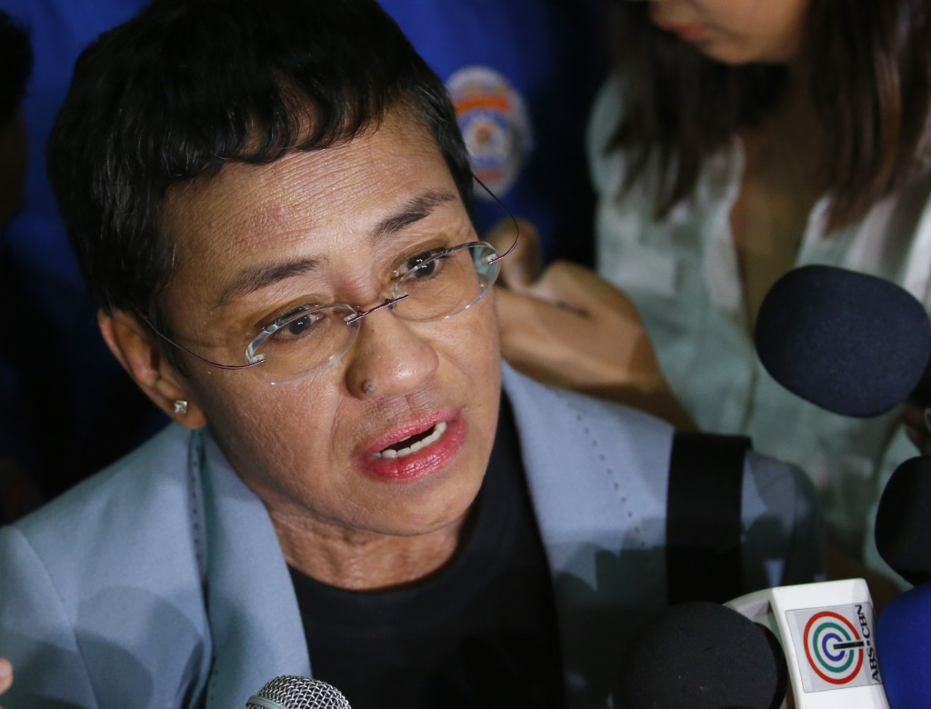 FILE - Maria Ressa, the award-winning head of a Philippine online news site Rappler, talks to the media after posting bail at a Regional Trial Court f...