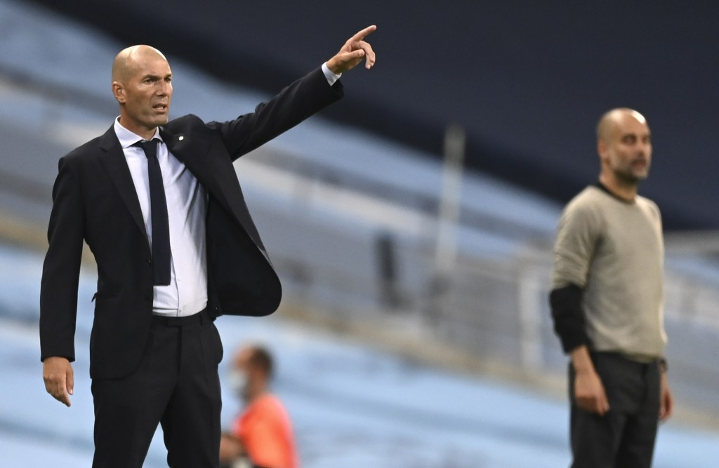 Real Madrid's head coach Zinedine Zidane, left, gestures as he stands alongside Manchester City's head coach Pep Guardiola during the Champions League...