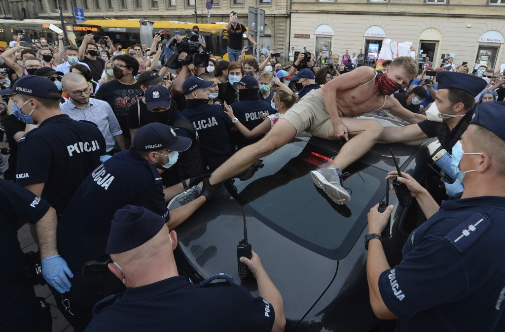 An activist climbs onto a police car to protest the detention of an LGBT activist in Warsaw, Poland, on Friday, August 7, 2020. The incident comes ami...