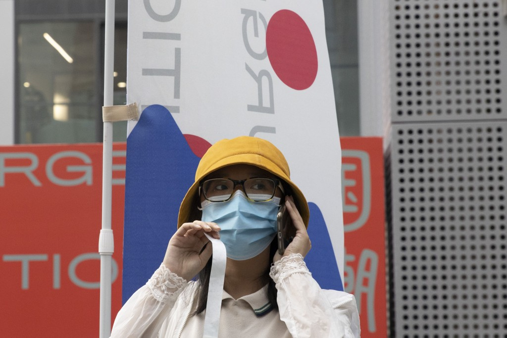 A woman wears a mask to prevent the spread of the coronavirus as she visits a weekend open air market in Beijing on Saturday, Aug. 8, 2020. As the cor...