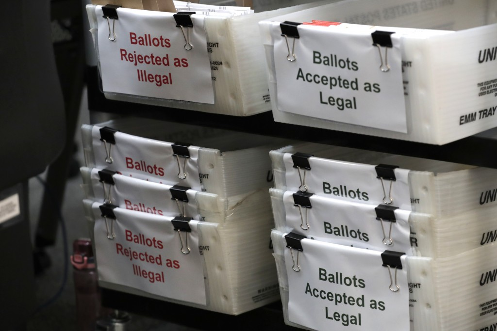 FILE - In this July 30, 2020, file photo, boxes for illegal and legal vote-by-mail ballots are shown as the the Miami-Dade County canvassing board mee...