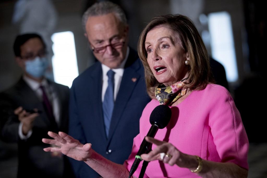 House Speaker Nancy Pelosi of Calif., center, accompanied by Senate Minority Leader Sen. Chuck Schumer of N.Y., left, speak to reporters following a m...