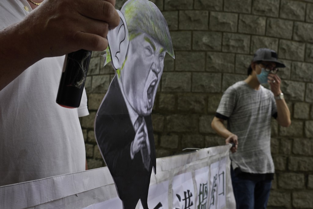 Pro-China supporters displays a picture of U.S. President Donald Trump during a protest against the U.S. sanctions outside the U.S. Consulate in Hong ...