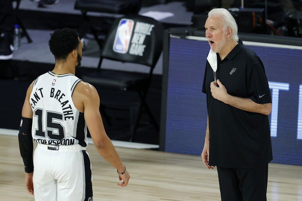 San Antonio Spurs head coach Gregg Popovich talks with Quinndary Weatherspoon (15) during the second half of an NBA basketball game against the Utah J...