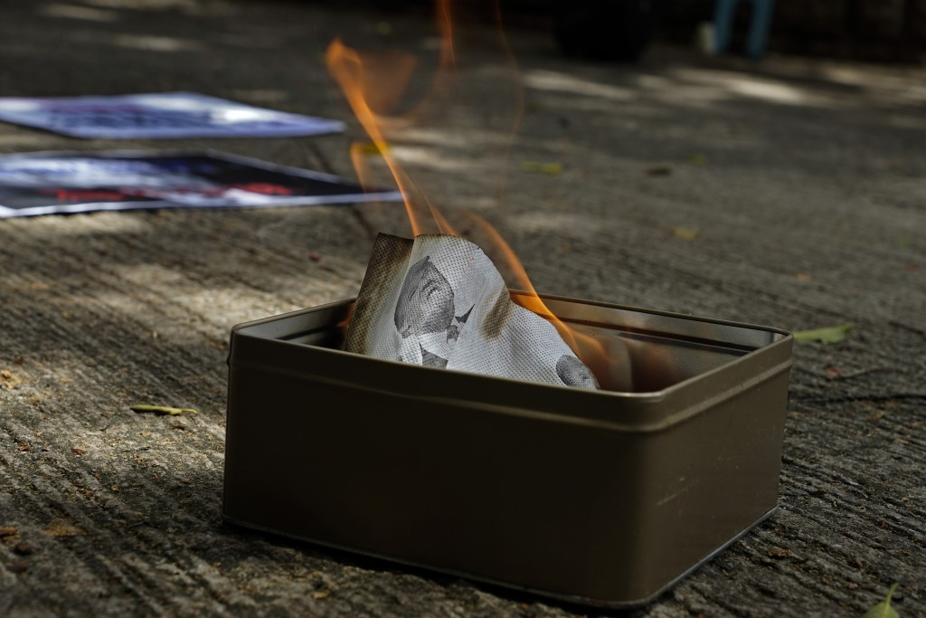 Pro-China supporters burn a picture of U.S. President Donald Trump during a protest against the U.S. sanctions outside the U.S. Consulate in Hong Kong...
