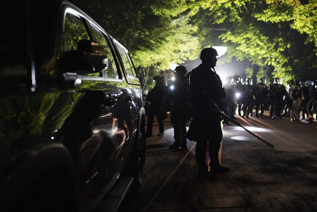 Portland police officers walk through the Laurelhurst neighborhood after dispersing protesters from the Multnomah County Sheriff's Office early in the...
