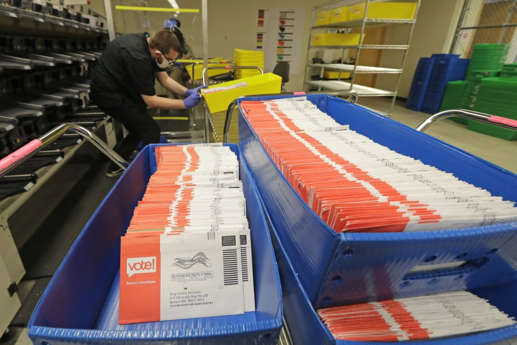 Vote-by-mail ballots are shown in sorting trays, Wednesday, Aug. 5, 2020, at the King County Elections headquarters in Renton, Wash., south of Seattle...