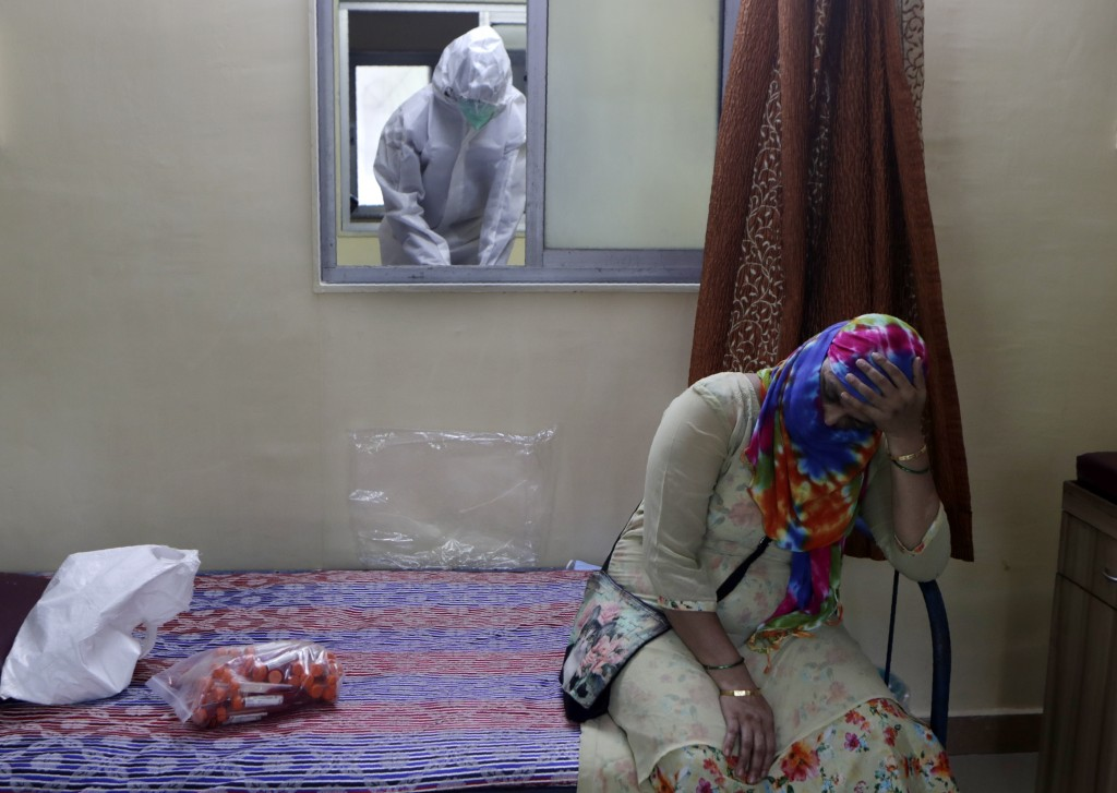 A woman waits to give a nasal swab sample to test for COVID-19 at a medical camp in Mumbai, India, Saturday, Aug. 8, 2020. As India hit another grim m...