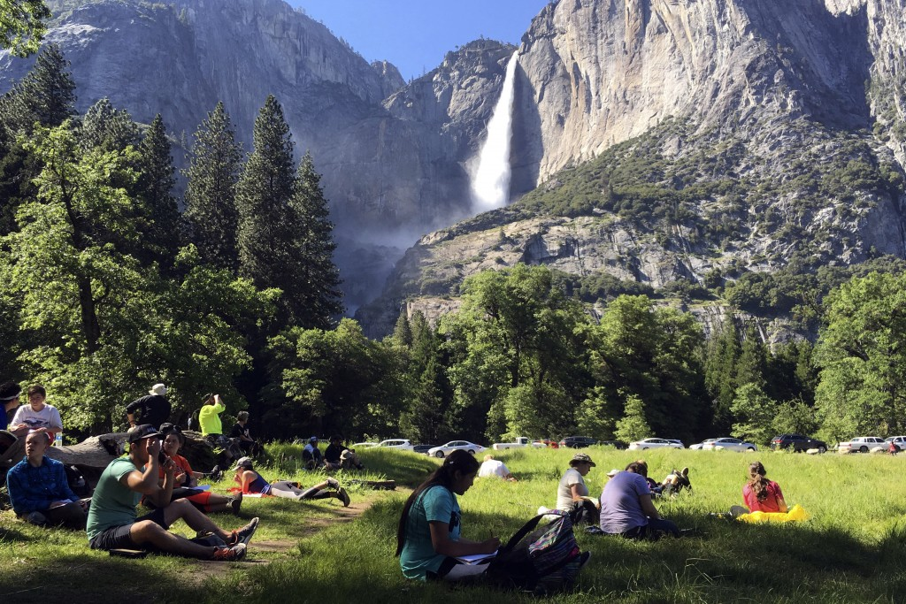 FILE - In this May 25, 2017 file photo, a class of eighth-grade students and their chaperones sit in a meadow at Yosemite National Park, Calif., below...