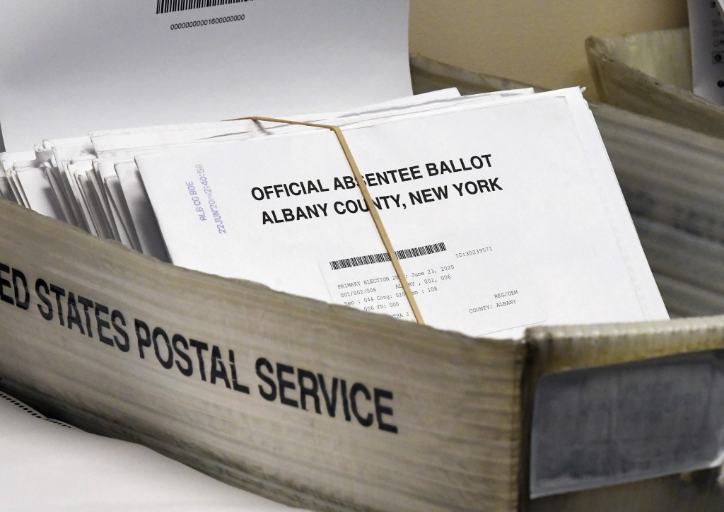 FILE - In this June 30, 2020, file photo, a box of absentee ballots wait to be counted at the Albany County Board of Elections in Albany, N.Y. Never b...