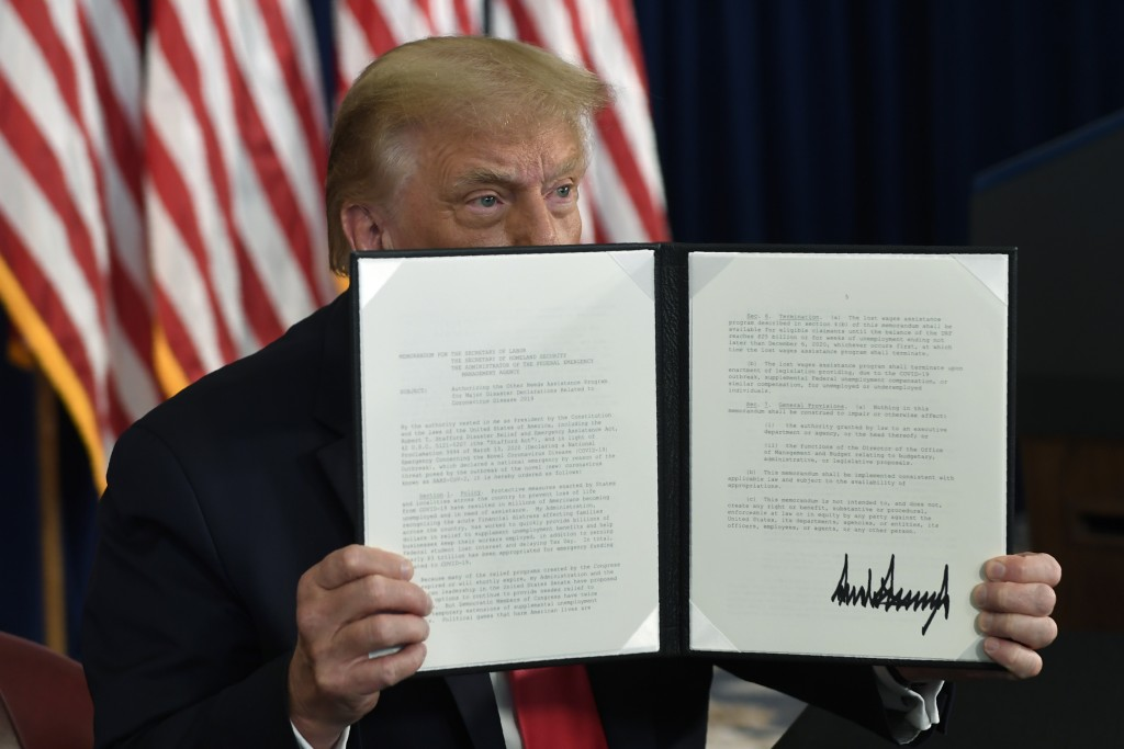 President Donald Trump signs an executive order during a news conference at the Trump National Golf Club in Bedminster, N.J., Saturday, Aug. 8, 2020. ...