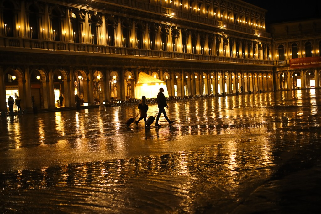 FILE - In this March 2, 2020, file photo, tourists pull their trolleys as they walk through a nearly empty St. Mark's Square on a rainy day in Venice....