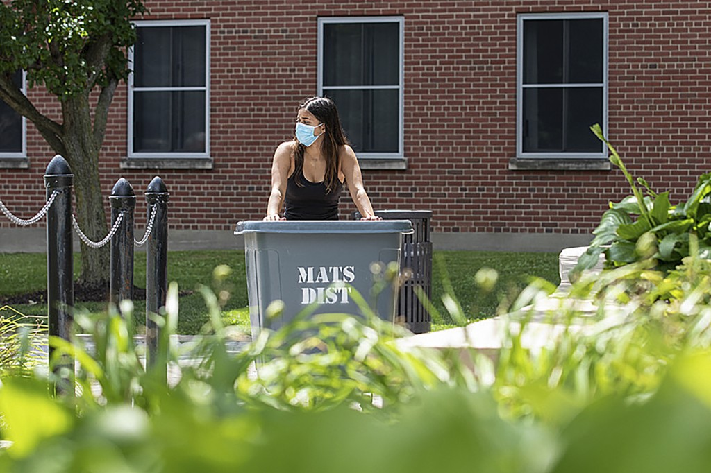 In this photo provided by Marilyn Hesler and Syracuse University, a student wearing a mask wheels her belongings up a ramp to move into her dorm, Sund...