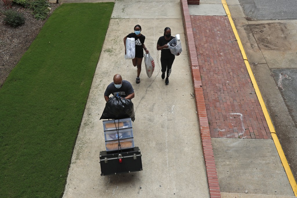FILE - In this July 31, 2020, file photo, a family carries their belongings while college students begin moving in for the fall semester at N.C. State...