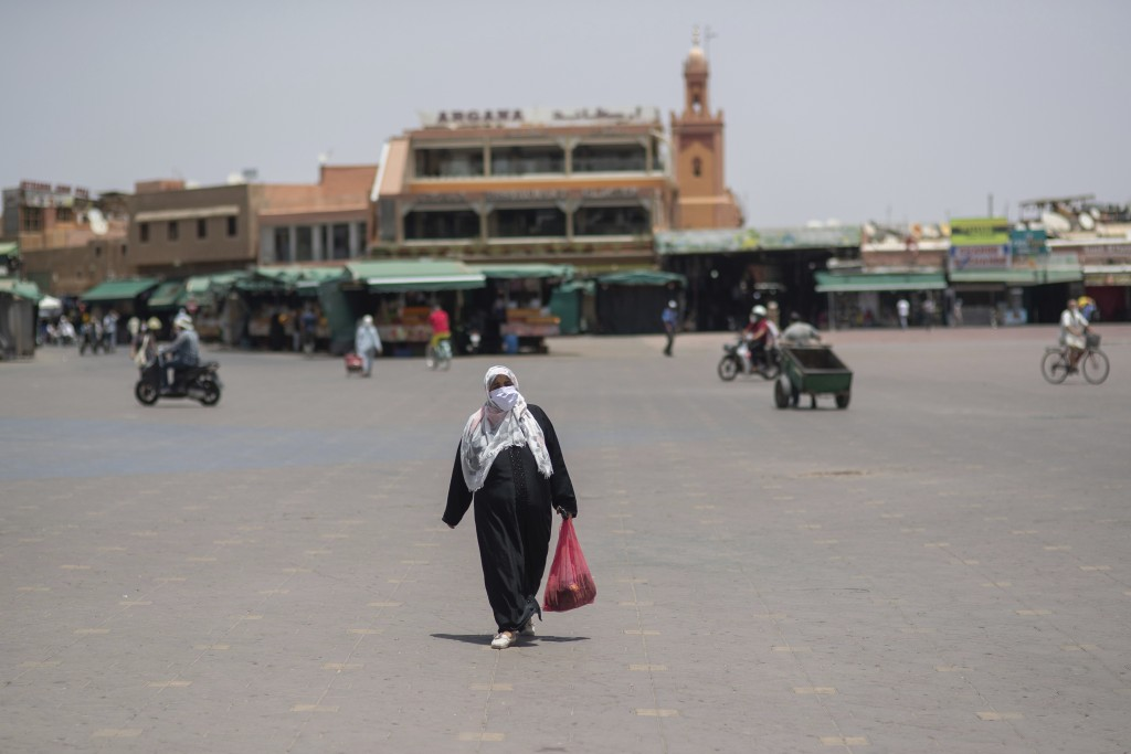 A woman walks with a grocery bag in the usually bustling landmark of Jemma el-Fnaa, in Marrakech, Morocco, Wednesday, July 22, 2020. Morocco's restric...