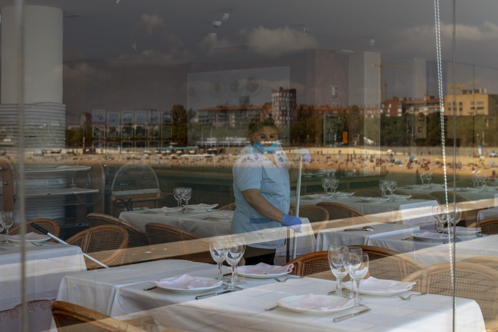 FILE - In this June 29, 2020, file photo, a woman cleans a restaurant prior to the opening, near the beach which is reflected in the glass, in Barcelo...