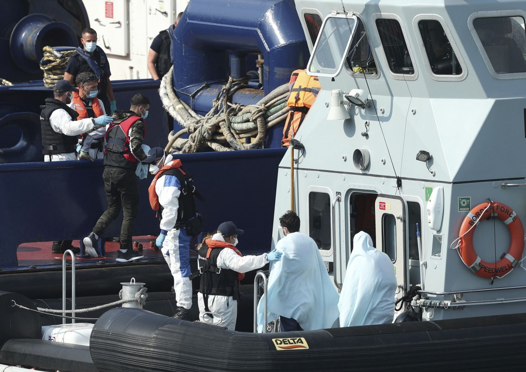 A Border Force vessel brings a group of people thought to be migrants into the port city of Dover, southern England, Sunday Aug. 9, 2020.  Many migran...