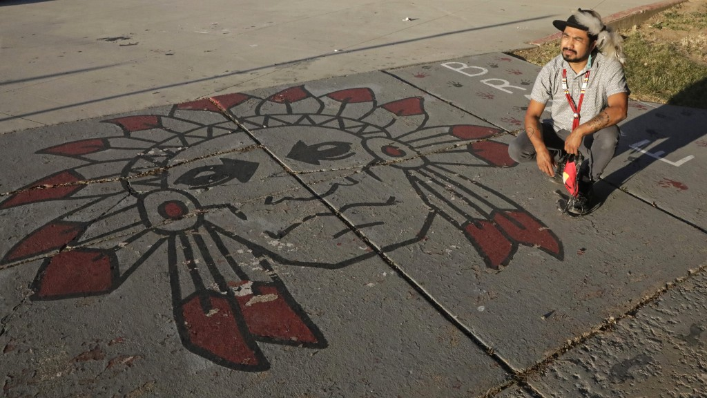 Native American advocate Carl Moore sits next to Native American imagery painted along a walkway which leads from the Bountiful High School parking lo...