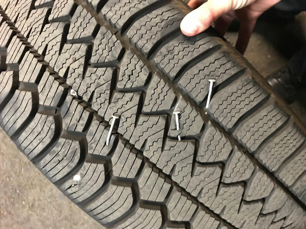 In this photo released Saturday, Aug. 8, 2020, by the Portland Police Department is a police vehicle tire that suffered damage from nail punctures, th...