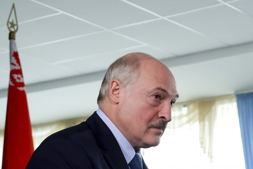 Belarusian President Alexander Lukashenko walks after voting at a polling station with a Belarusian national flag on the left, during the presidential...
