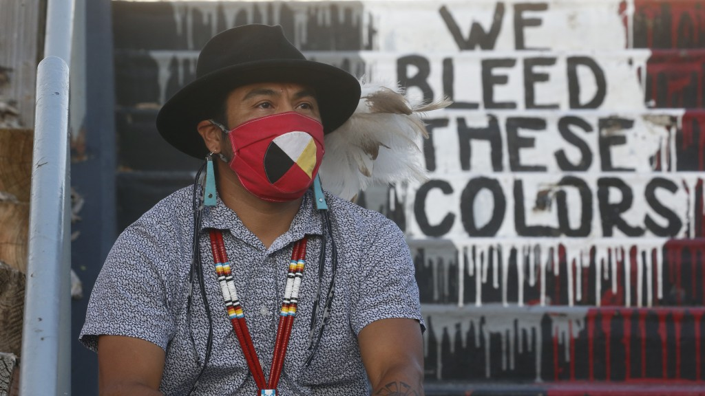 """Native American advocate Carl Moore sits near the phrase """"We Bleed These Colors"""" along a walkway which leads from the Bountiful High School parking lo..."""