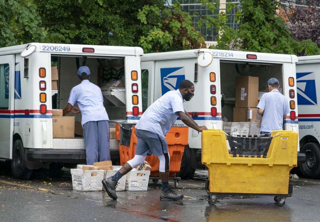 FILE - In this July 31, 2020, file photo, letter carriers load mail trucks for deliveries at a U.S. Postal Service facility in McLean, Va. The success...