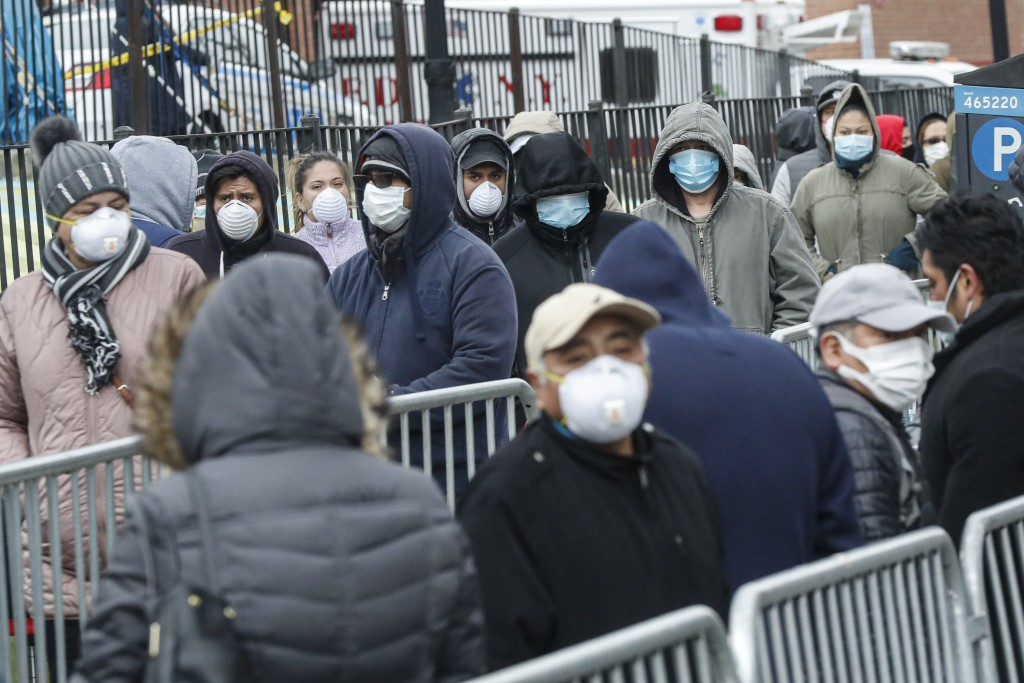 FILE - In this March 25, 2020, file photo, patients wear personal protective equipment while maintaining social distancing as they wait in line for a ...