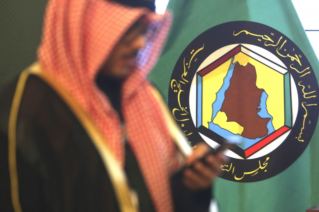 FILE - In this Dec. 5, 2017 file photo, a man looks at his mobile phone in front of the flag of the Gulf Cooperation Council, GCC, in Kuwait City. The...