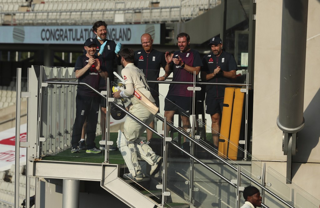 Members of team support staff cheer for England's Chris Woakes after their win on the fourth day of the first cricket Test match between England and P...
