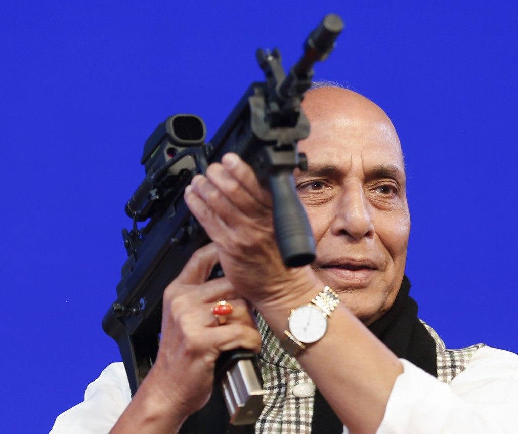 FILE- In this Feb. 7, 2020 file photo,  Indian Defense Minister Rajnath Singh holds a model of a light machine gun during DefExpo20 in Lucknow, India....