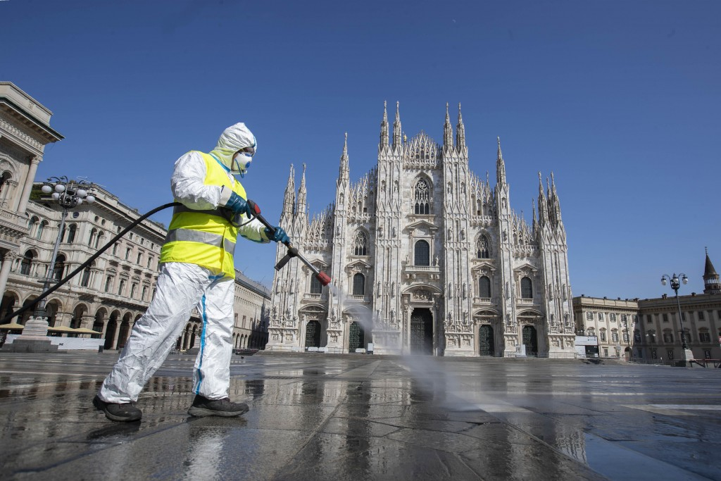 FILE - In this March 31, 2020, file photo, a worker sprays disinfectant to sanitize Duomo square, as the city main landmark, the gothic cathedral, sta...