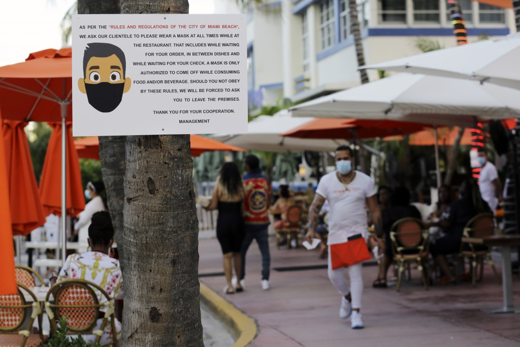FILE - In this July 24, 2020, file photo, a sign informs customers at the Edison Hotel restaurant about wearing a protective face mask during the coro...
