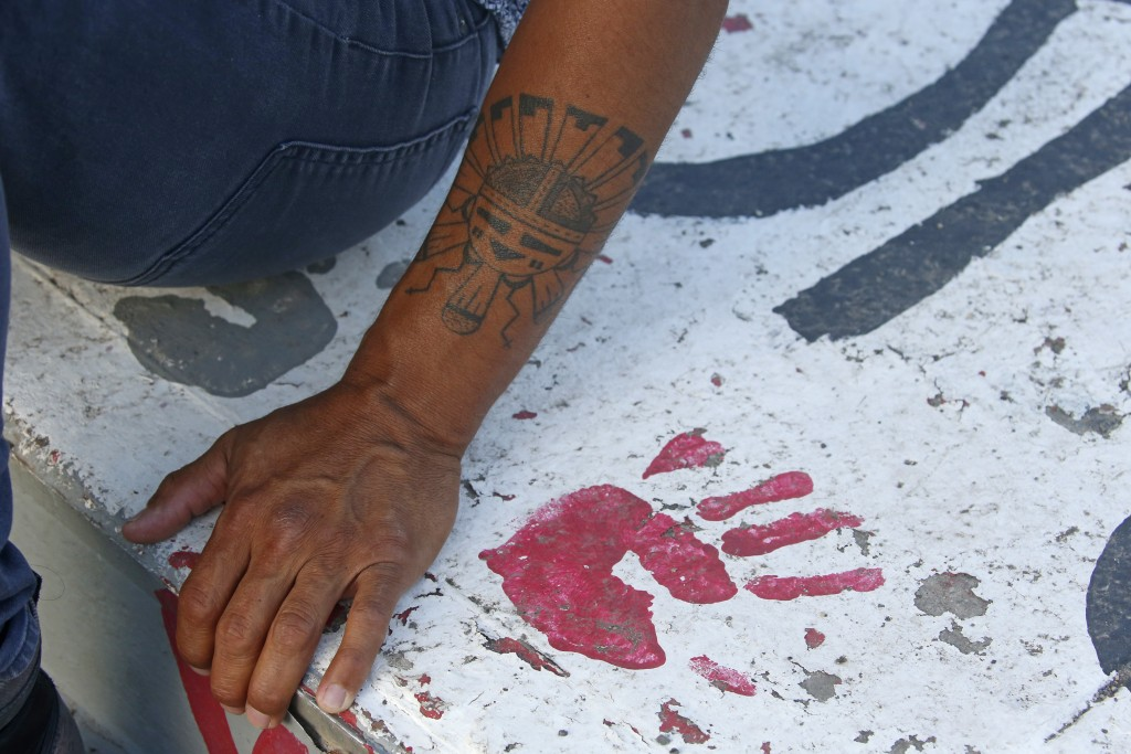 Native American advocate Carl Moore sits next to red handprint painted along a walkway which leads from the Bountiful High School parking lot up to th...