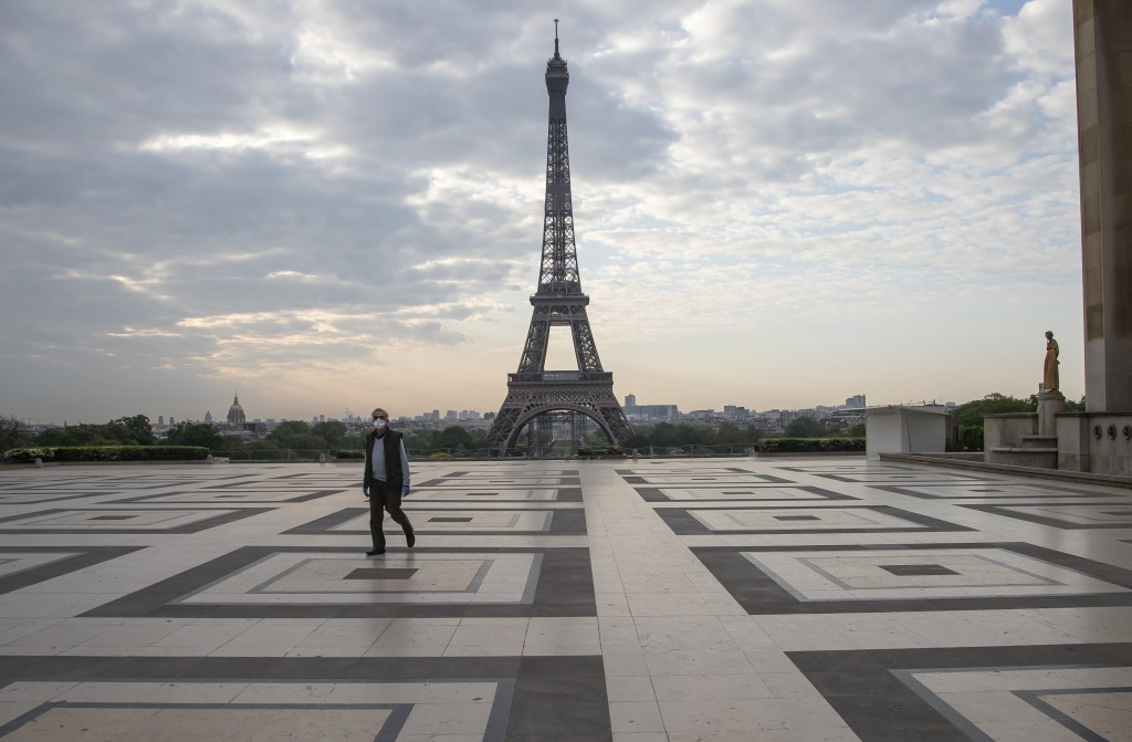 In this April 24, 2020, file photo, a man wears a mask to protect against the spread of the coronavirus as he walks along the Trocadero square close t...