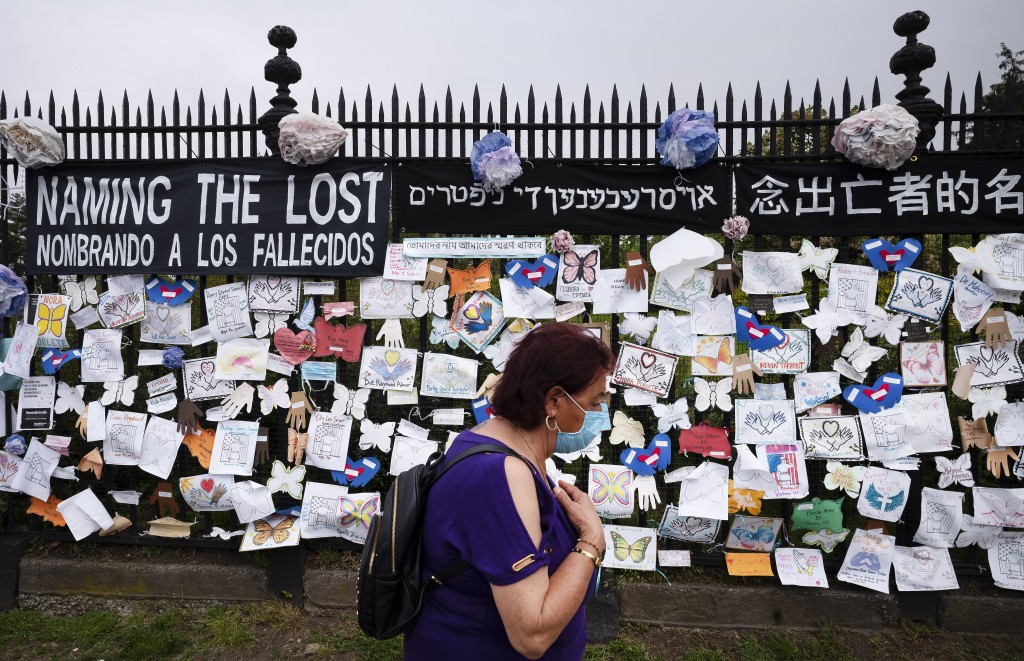 FILE - In this May 28, 2020, file photo, a woman passes a fence outside Brooklyn's Green-Wood Cemetery adorned with tributes to victims of COVID-19 in...