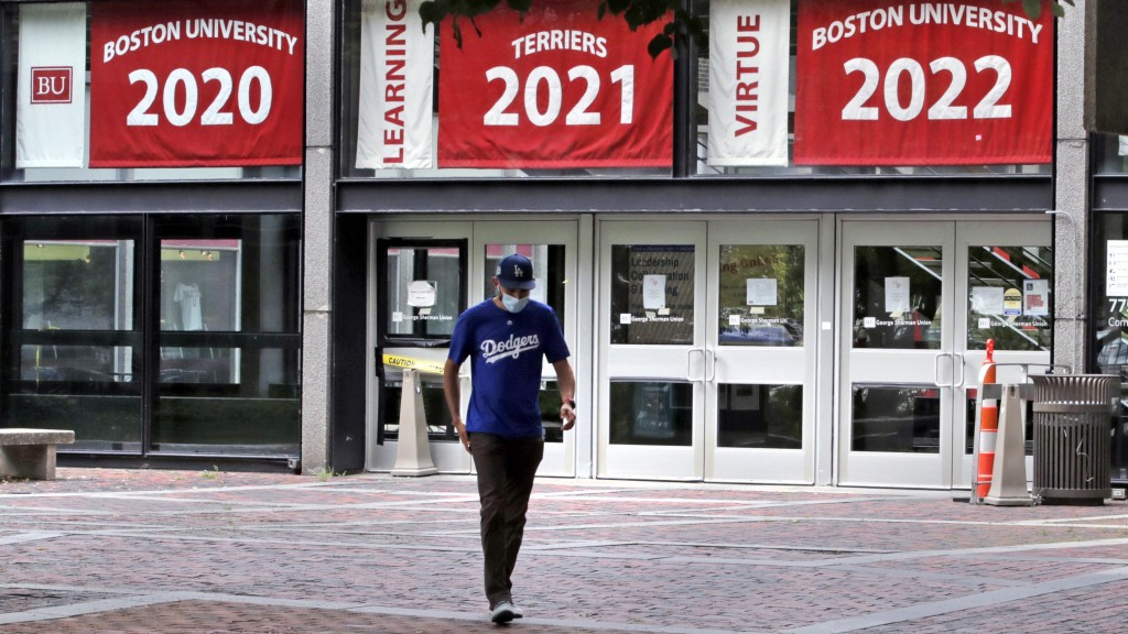 FILE - In this July 23, 2020, file photo, Weston Koenn, a graduate student from Los Angeles, leaves the Boston University student union building as he...