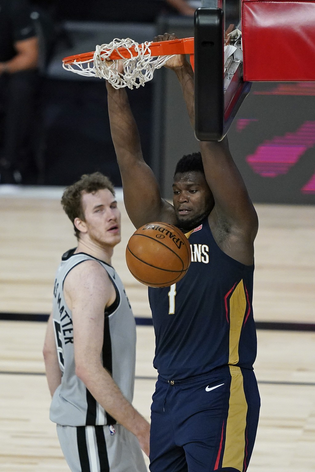New Orleans Pelicans forward Zion Williamson, right, dunks the ball in front of San Antonio Spurs center Jakob Poeltl during the second half of an NBA...
