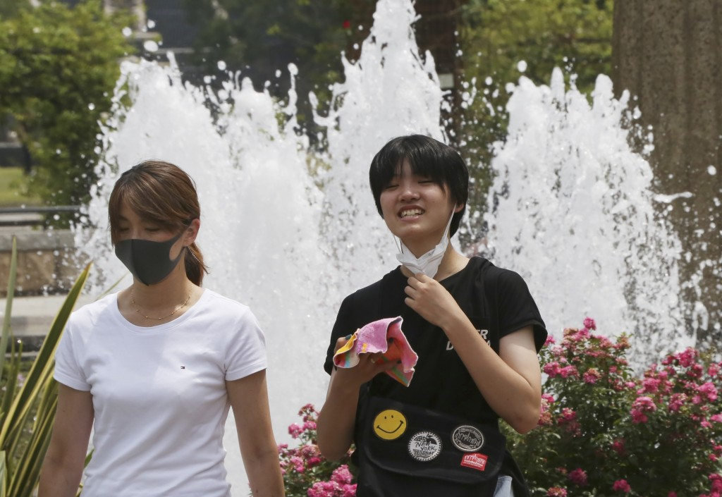 People wearing face masks to protect against the spread of the new coronavirus walk at park in Yokohama near Tokyo, Monday, Aug, 10, 2020. (AP Photo/K...