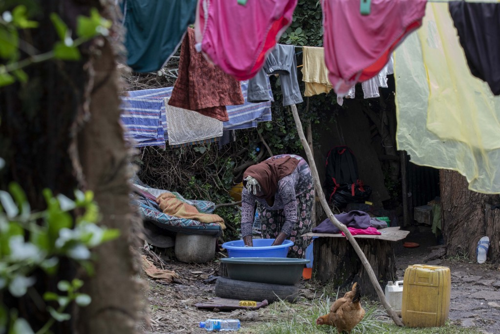 Mother of two Amsale Hailemariam, a domestic worker who lost work because of the coronavirus, washes her family's clothes outside her small tent in th...