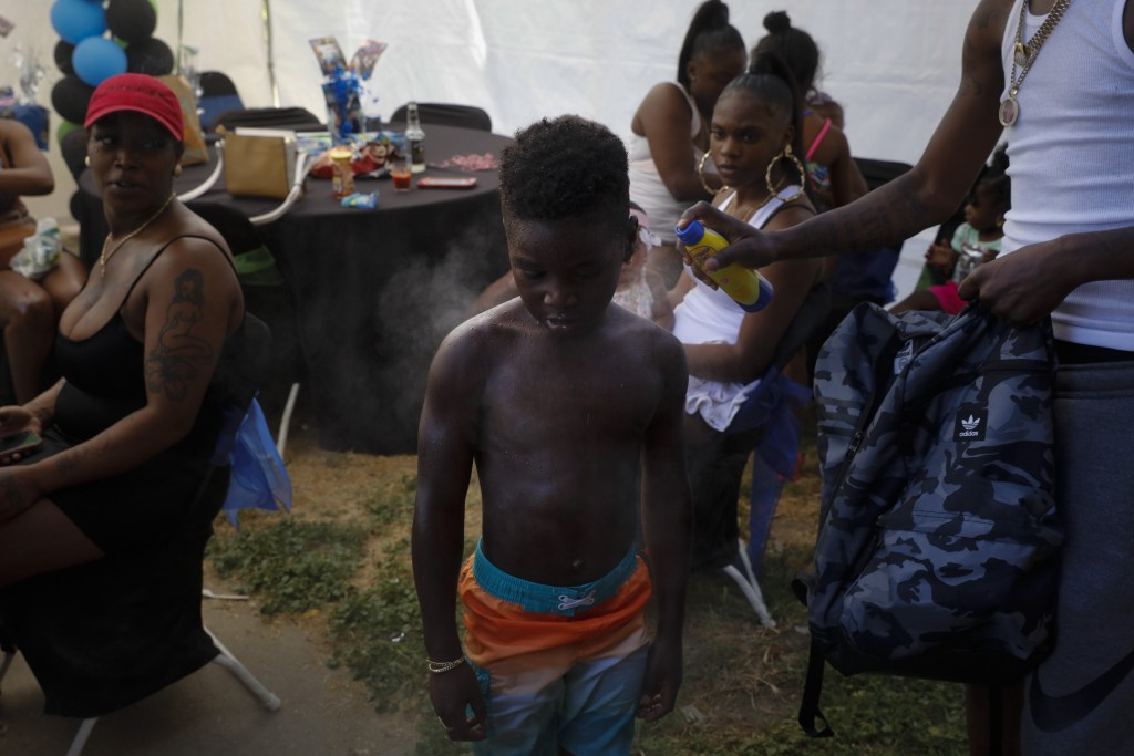 Emmett Palmer, right sprays sunscreen on Iron Grim, 6, as tenants gather for a birthday party at the Nickerson Gardens housing project in the Watts ne...