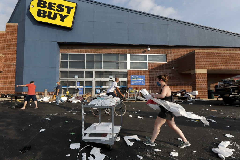 Volunteers help clean up the parking lot outside a Best Buy store, Monday, Aug. 10, 2020, after vandals struck overnight in the Lincoln Park neighborh...