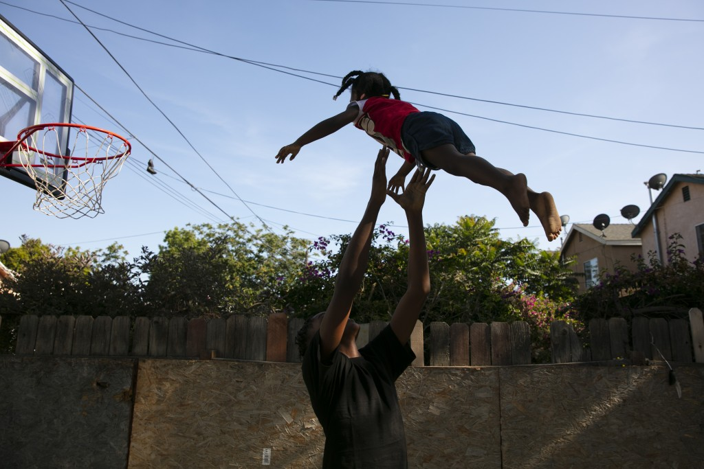 James Posey III, 14, tosses a neighbor's kid in the air while playing with her in the Watts neighborhood of Los Angeles, Monday, June 15, 2020. Watts ...