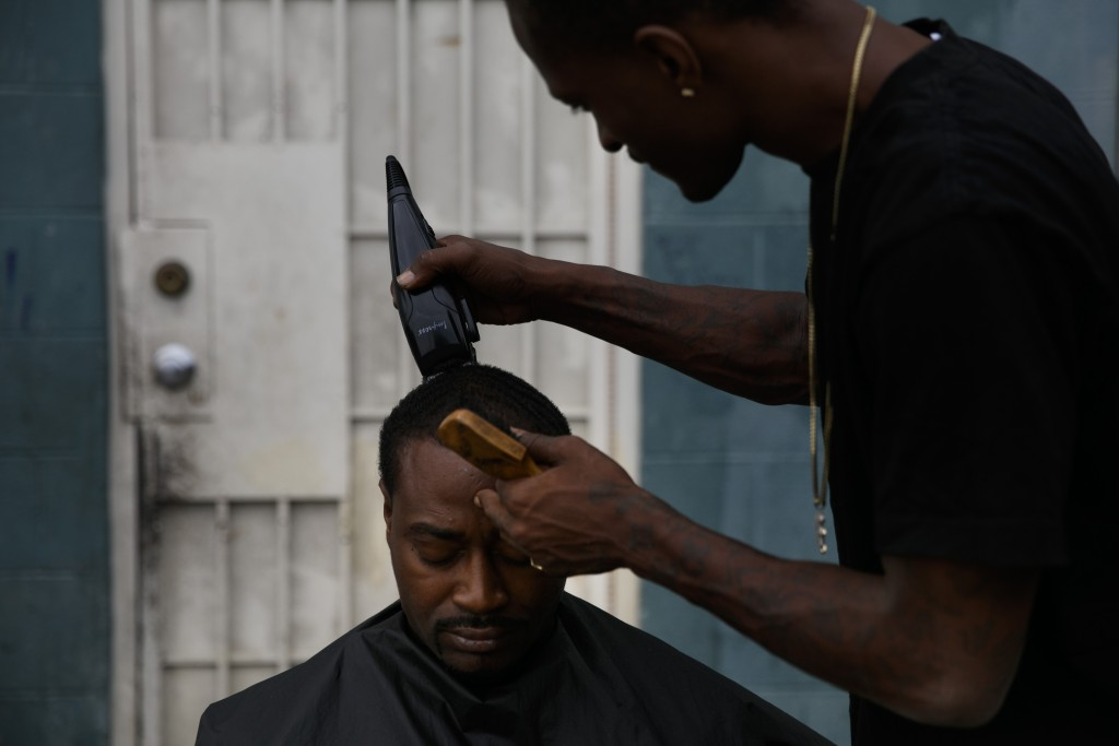 Eric Frierson, 37, gets an haircut from Kenneth Cox, 32, outside an apartment building at the Imperial Courts housing project in the Watts neighborhoo...