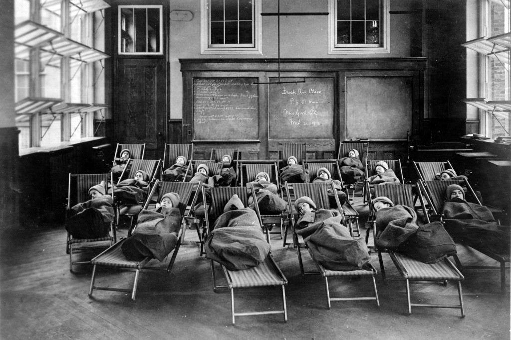 This 1911 photo from the Library of Congress shows children wrapped in blankets, at a fresh air class rest hour at Public School No. 51, in New York. ...
